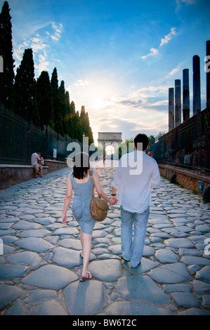 Couple walking together toward Arco di Settimio Severo in the. Roman Forum. - Stock Photo