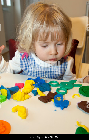 young three year old girl playing with play dough activity - Stock Photo