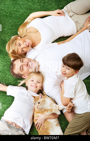 Above view of family members with pet lying on green grass and smiling at camera - Stock Photo