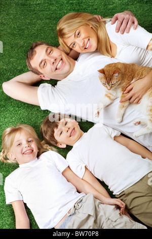 Above view of family members with pet lying on green grass and having rest - Stock Photo