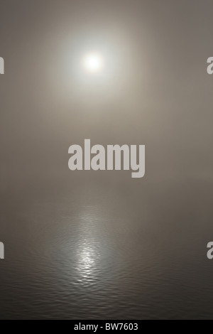The sun reflecting on a misty lake - Stock Photo