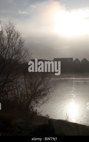 A foggy morning at a lake with houses in the distance, the sun shimmering on the water. - Stock Photo
