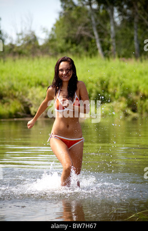 Portrait of slim woman wearing swimsuit running in the lake - Stock Photo