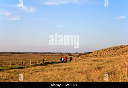 Walkers on a public footpath on the landward side of sand dunes at Horsey, Norfolk, England, United Kingdom. - Stock Photo