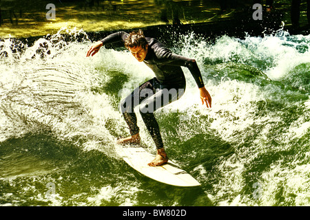 Surfing on Isar river, on the Eisbach wave, near the Haus der Kunst , a  new tourist attraction in Munich, Germany. - Stock Photo