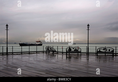 Southend Pier, Southend on Sea, Essex, Britain. freighters moored off the end of the pier waiting for the tide. - Stock Photo