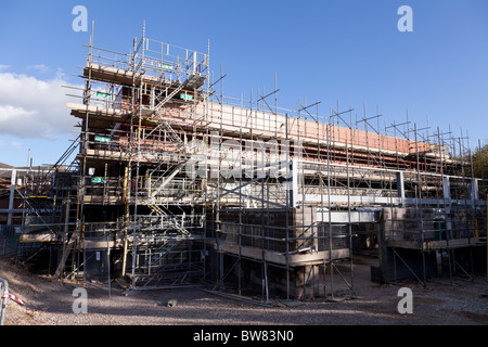 scaffolding covering new building under construction - Stock Photo