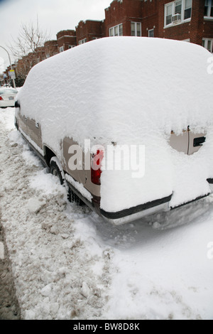 snow surrounds and covers and SUV car parked on a plowed city side street in winter - Stock Photo