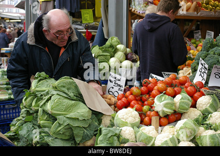 Browsing for fruit and vegetables at Bury Market - Stock Photo