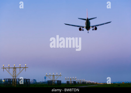 Amsterdam Schiphol Airport at dusk. Airplane plane approaching, landing, on the Kaagbaan runway. - Stock Photo