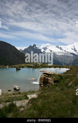 Alpine lake at Kreuzboden above the Saastel valley looking towards the Allalinhorn, Switzerland - Stock Photo
