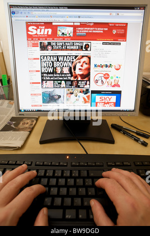 Office working reading The Sun newspaper online - Stock Photo