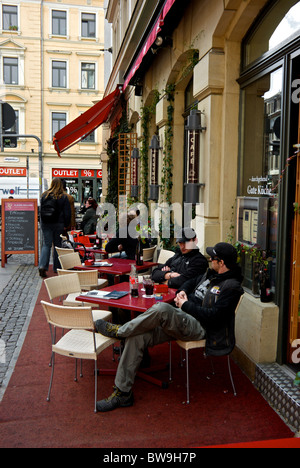 Visitors enjoying drink on sidewalk patio cafe in funky hip Dresden new town Neustadt home to some 250 bars restaurants - Stock Photo