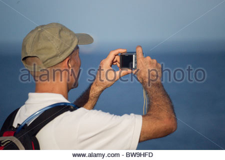 Amateur photographer  holding a compact digital camera to take a photo - Stock Photo