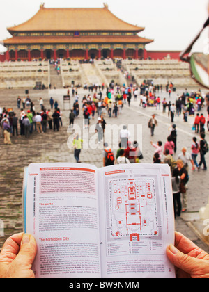 Tourist reading guide book whilst in the Forbidden City, Beijing - Stock Photo
