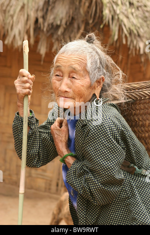 Hmong elderly woman carrying a basket in a small village between Pakbeng and Luang Prabang, Laos. - Stock Photo