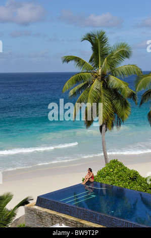 Woman sitting at swimming pool of the Hotel Banyan Tree, Mahé Island, Seychelles - Stock Photo