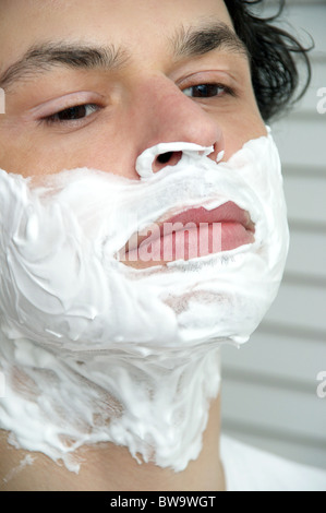 Young man with shaving foam on his face - Stock Photo