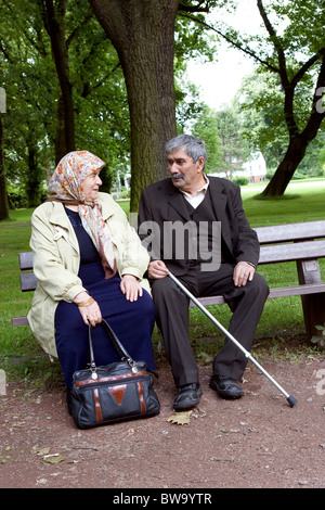 An elderly Turkish couple sitting on a bench in a park, Herne, Germany - Stock Photo