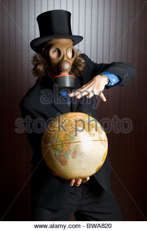 Businessman wearing a gas mask holding an earth globe - Stock Photo
