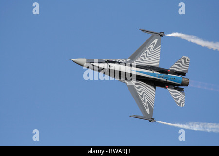 Belgian F-16 fighter jet plane flying in the sky during an air display. Underside view. Off centre composition with copy space.