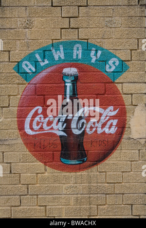 Classic coca-cola stencil ad on a wall in Brooklyn, New York with a hand written addition on it. - Stock Photo
