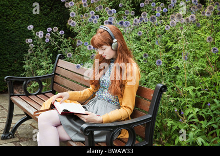 Woman reading,sitting on bench in park - Stock Photo