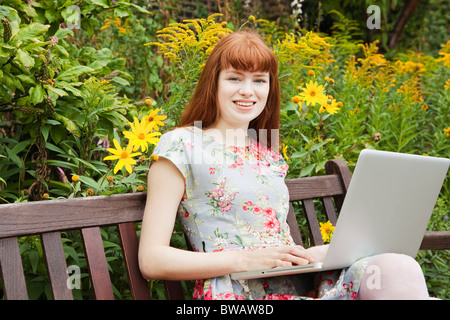Woman working  on laptop on parkbench - Stock Photo