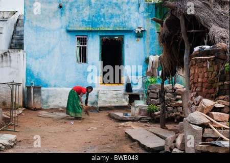Young indian girl sweeping the front yard of her home in a rural indian village. Andhra Pradesh, India - Stock Photo