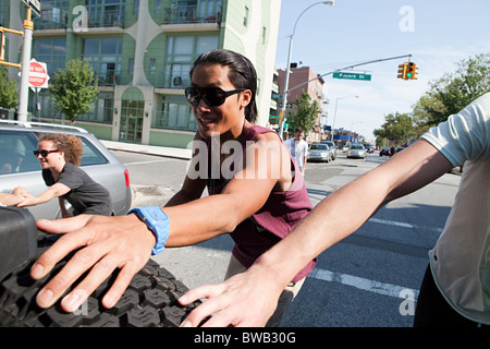 Skateboarders holding on to tyre on back of car - Stock Photo