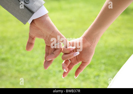Close-up of bride's hand holding that of her husband over green background - Stock Photo