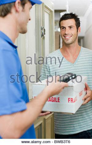 Delivery man delivering parcel - Stock Photo