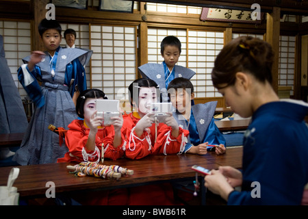 Children dressed in  traditional Japanese clothes playing nintendo games at Kitano Tenman-gu Shrine Kyoto Japan - Stock Photo