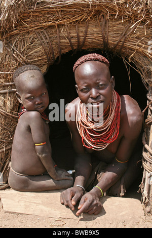 Karo Tribe Woman With Baby In The Entrance To Her Hut, Omo Valley, Ethiopia - Stock Photo