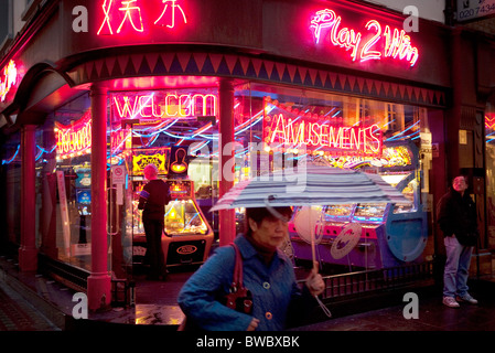 Night time scene outside an amusements arcade in Chinatown. Here people can bet on small gaming machines and play - Stock Photo