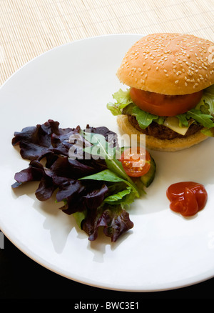 Food, Cooked, Hamburger, Single quarter pound cheeseburger with tomato and lettuce in a bun on a white plate with - Stock Photo