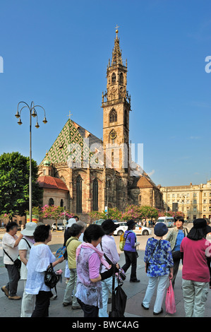 Chinese tourists and Gothic cathedral / Duomo di Bolzano at the Piazza Walther in Bolzano / Bozen, Dolomites, Italy - Stock Photo