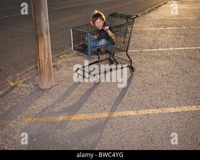 Boy using shopping cart as a vehicle - Stock Photo