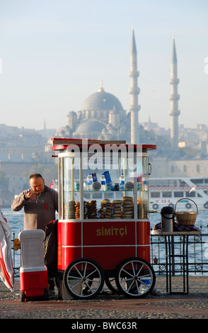 ISTANBUL, TURKEY. One of Istanbul's ubiquitous licensed simit vendors, with the Golden Horn and Yeni Mosque behind. - Stock Photo