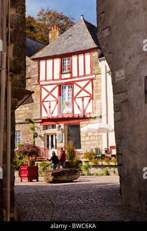 Couple walking past a medieval house in Rochefort en Terre, Morbihan, Brittany France Europe - Stock Photo