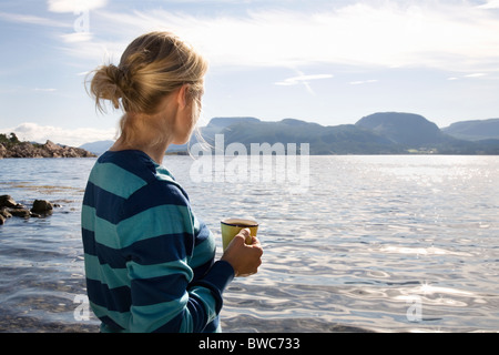 Woman with coffee by sea and mountains - Stock Photo