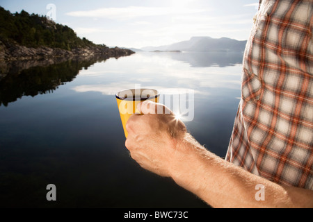 Man having coffee by sea and mountains - Stock Photo