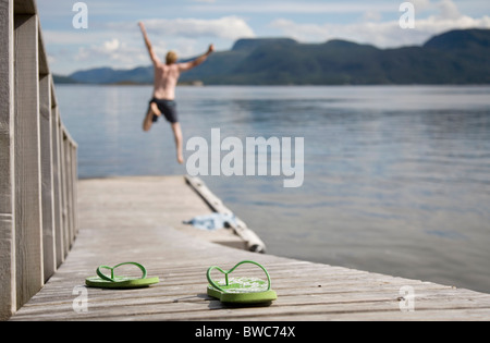 Man jumping off wooden jetty into sea - Stock Photo