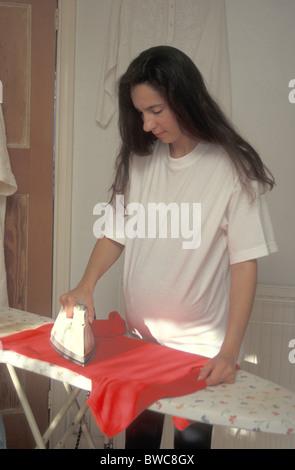 pregnant woman ironing - Stock Photo