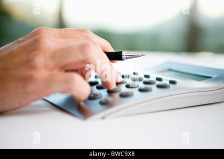 Businessman using calculator, close-up - Stock Photo