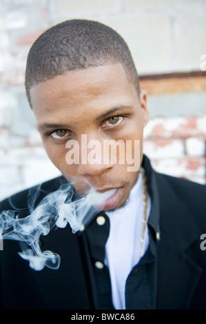 USA, Illinois, Peoria, Portrait of young man smoking - Stock Photo