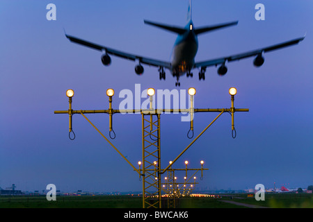 KLM airplane plane approaching, landing, on the Kaagbaan runway of Amsterdam Schiphol Airport at dusk. - Stock Photo