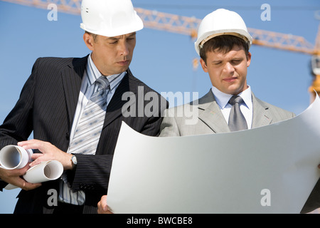 Portrait of two architects looking at project on construction site - Stock Photo