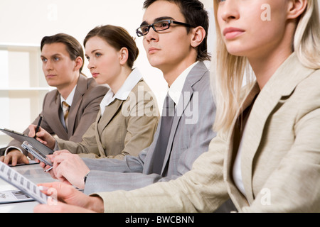 Serious students sitting in row and looking at board during presentation - Stock Photo