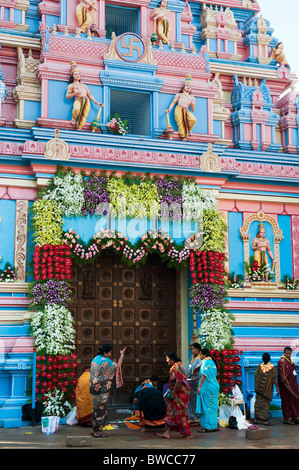 Indian women decorating Sathya Sai Babas Gopuram temple entrance with flowers and rangoli in the Indian town of - Stock Photo